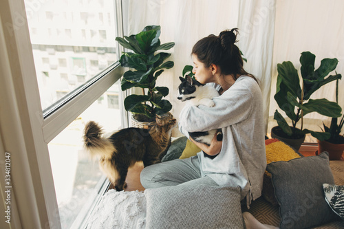 Fototapeta Hipster girl hugging and playing with two cats in modern room, sitting together at home during coronavirus quarantine. Stay home stay safe. Isolation at home to prevent virus epidemic. obraz