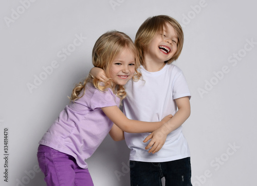 Leinwand Poster Little blond baby girl and boy friends or sister and brother in stylish clothing