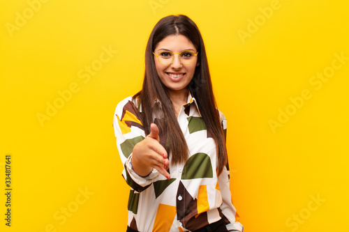 Photo young pretty woman smiling, looking happy, confident and friendly, offering a ha