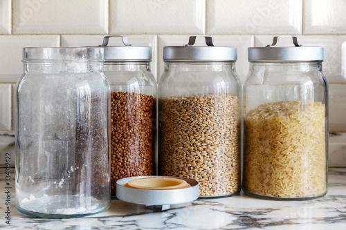 Fényképezés glass jars with rice, buckwheat, barley and an empty sugar jar