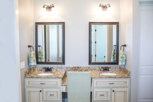 Large Neutral Cream Colored Master Bathroom With Double Sinks, Two Mirrors And A Granite Countertop In A New Construction Modern Home