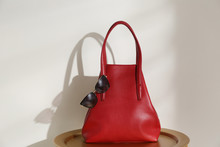 Stylish Red Woman's Bag And Sunglasses On Table Near Light Wall