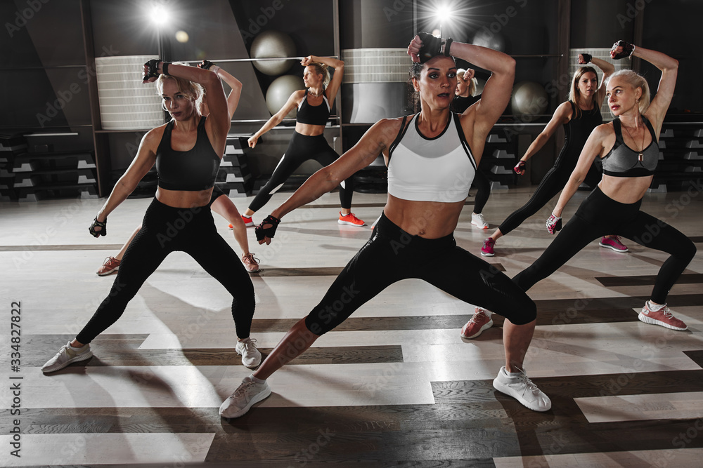 Fototapeta Women in black and white sportswear on a real group body Combat workout in the gym train to fight, kickboxing with a trainer