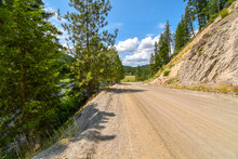 A Rural Dirt Road With A Steep Mountain On One Side And A Ravine On The Other In The Mountains Of The Coeur D'Alene Area In North Idaho, USA.