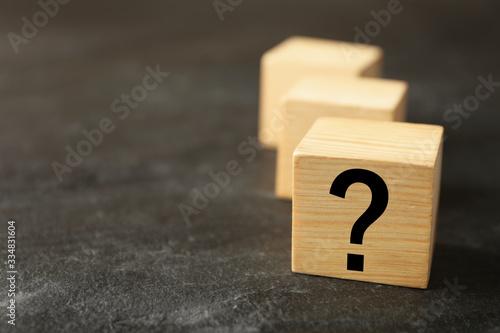 Obraz na plátně Cube with question mark on grey stone table, closeup