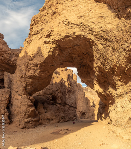 Fotografija A natural arch bridge in a narrow canyon cut into a layer of conglomerate rock b