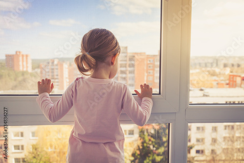 Obraz Little girl looking outside through the window - fototapety do salonu