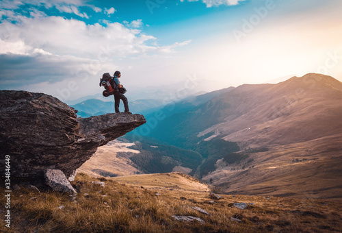 Fototapeta hiker with a big backpackon the edge of a cliff admiring an epic landscape obraz