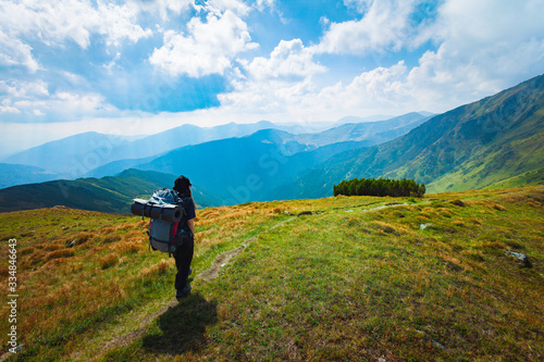 Stampa su Tela Hiking trough epic mountain landscape with a big backpack, exploring and feeling
