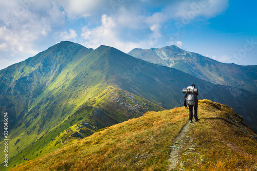 Fototapeta Hiking trough epic mountain landscape with a big backpack, exploring and feeling