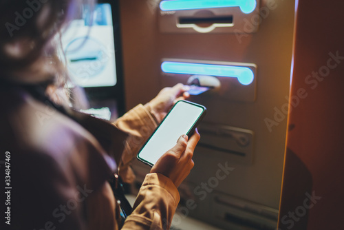 Photo Woman using street ATM machine to withdraw money inserting a credit card while s