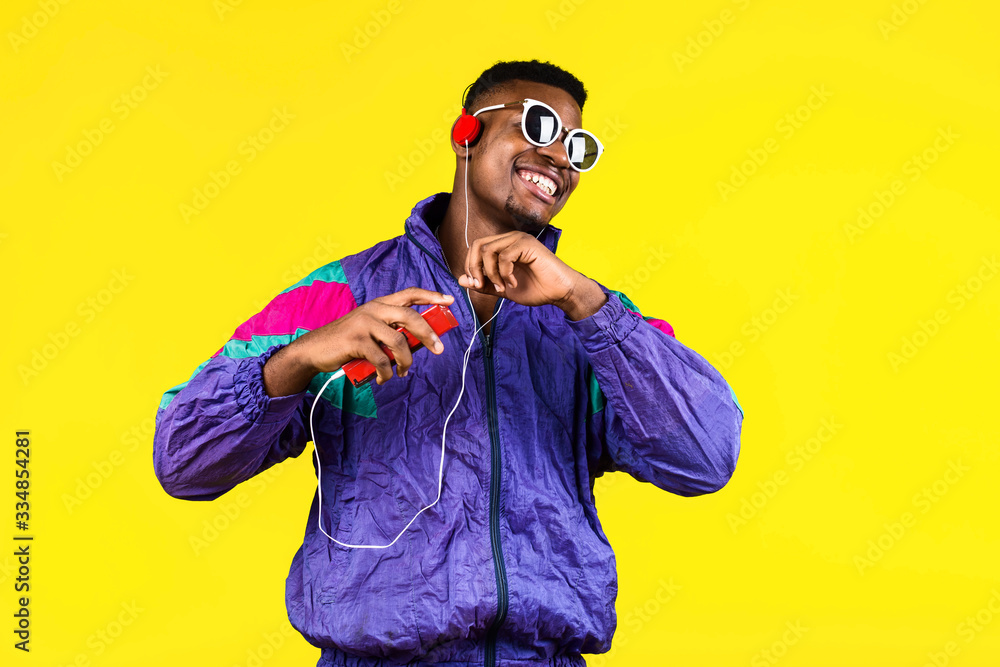 Fototapeta African American young man, in a jacket in the style of the 90s, with a retro cassette player, hears music, the mood of dancing and fun, yellow and purple colors