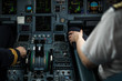 Pilot's hand dialing in flight values in a commercial airliner airplane flight cockpit during takeoff