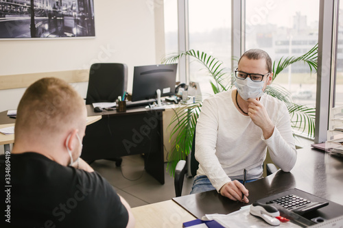 Fotografiet an office worker in a protective mask talks to a client