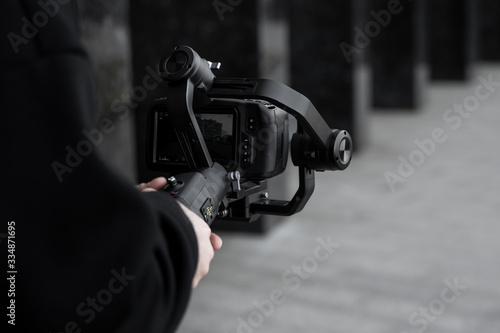 Fényképezés Professional videographer in black hoodie holding professional camera on 3-axis gimbal stabilizer