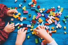 Children Play And Build With Colorful Toy Bricks, Plastic Blocks.