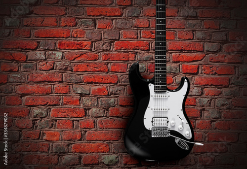 Fotografiet Black electric guitar on red brick wall background