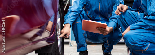 Fototapeta banner of automotive mechanic men checking at  car tyre rubber condition needed for replacement, man pointing hand at wheel following maintenance checklist document, after service at auto repair shop obraz