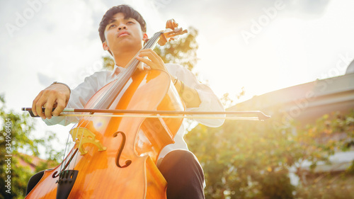 Foto Musician man using a bow to practicing the cello playing with the melodiousness at the sunset