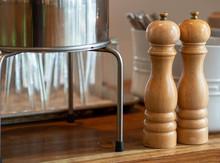 Wooden Hand Crank Salt And Pepper Shaker On Table Near Utensils And Glasses