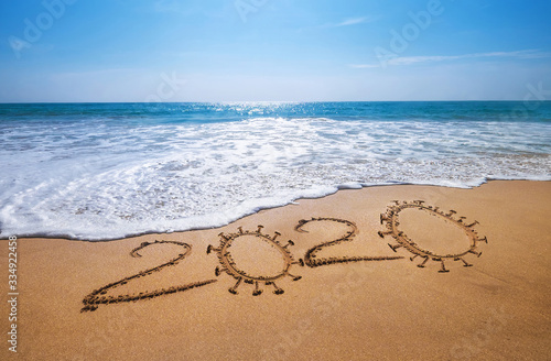 Obraz Year 2020  Global COVID-19 pandemic concept image. Sandy tropical ocean beach lettering. SARS-CoV-2 beating and vaccine researching concept image. - fototapety do salonu