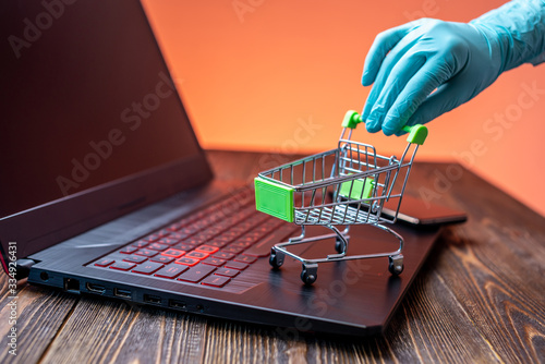 Foto Hand in a sterile glove holds a shopping cart with a credit card