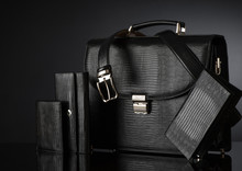 Fashionable Men's Set Of Leather Accessories On A Dark Background. Briefcase, Wallet, Belt