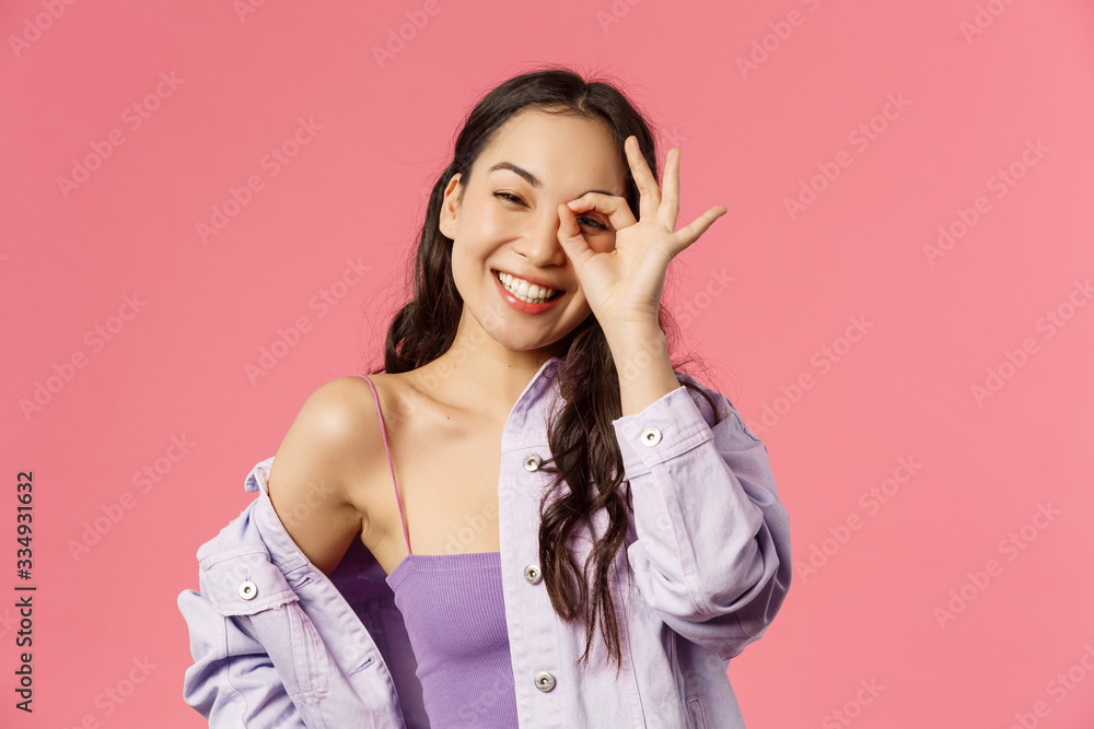 Fototapeta Close-up portrait of carefree, optimistic good-looking asian girl in stylish outfit, korean female student have positive happy mood, show okay no problem sign over eye, grinning joyfully