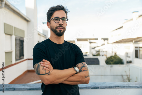 Fotomural Confident stylish guy with tattoos posing on apartment balcony or terrace