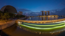 Skyline In Marina Bay With Esplanade Theaters On The Bay And Esplanade Footbridge Night To Day Timelapse In Singapore.