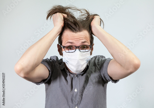 A young man in a medical mask respirator is holding head with hands on a gray background Canvas Print