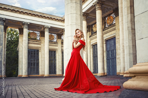 Fotografiet Beautiful blonde girl in a red long dress on a background of architecture, colum