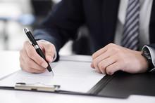 書類にサインする日本人男性ビジネスマンの手元