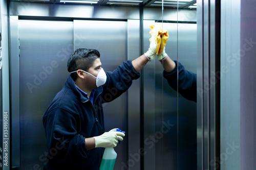 Fototapeta coronavirus. cleaning staff disinfecting elevator to avoid contagion obraz
