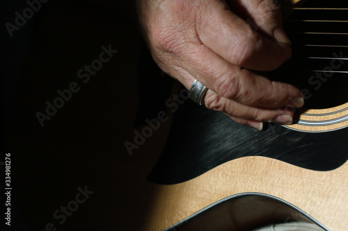 close up of old man playing an acoustic guitar wearing a ring. Fototapeta