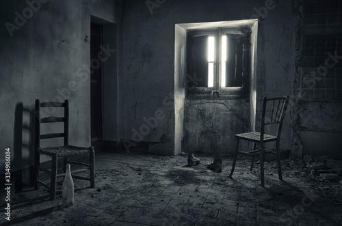 Canvastavla Habitación de casa abandonada con sillas iluminadas en la penumbra por una ventana