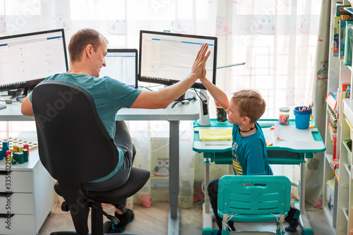 Fototapeta Father with kid working from home during quarantine. Stay at home, work from home concept during coronavirus pandemic obraz