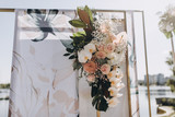 Arch design for the wedding ceremony is decorated with flower arrangements and stands on the lake background and Yacht Club