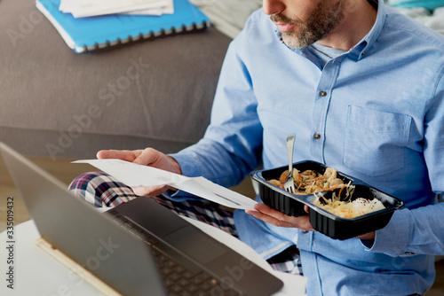 Foto Man working home with food taken away.