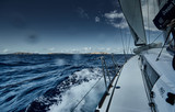 The view of the sea and mountains from the sailboat, edge of a board of the boat, slings and ropes, splashes from under the boat, sunny weather, dramatic sky