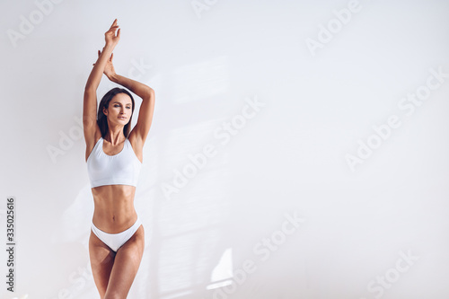 Obraz Young fit woman in white lingerie on white background isolated. Muscular slim attractive female with flat belly. Copy space for text. Body care, healthy and sporty life, hair removal, yoga concept - fototapety do salonu
