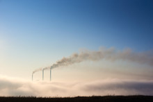 Tops Of Three Smoking Stacks Of Thermal Power Station On Horizon Taken From The Hill, Pipes In Morning Fog On Blue Sky, Concept Of Dangerous Emission In Atmosphere, Ecology, Environmental Pollution