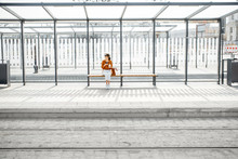 Woman Sitting Alone At The Public Transport Stop On A Sunny Day Outdoors, General Plan On A Modern Stop. Concept Of A Transportation And Urban Life