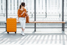 Young Female Traveler Sitting With A Suitcase At The Transport Stop, Waiting For The Tram Or Bus. Direct Angle View On A Stop Bench. Concept Of A City Transportation And Travel