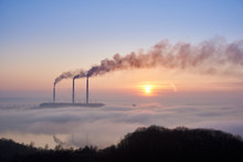 Horizontal Snapshot Of Three Smoking Stacks Of Thermal Power Station On The Horizon Taken From The Hill, Pipes Are In Evening Fog On Blue Sky, Copy Space. Concept Of Environmental Pollution