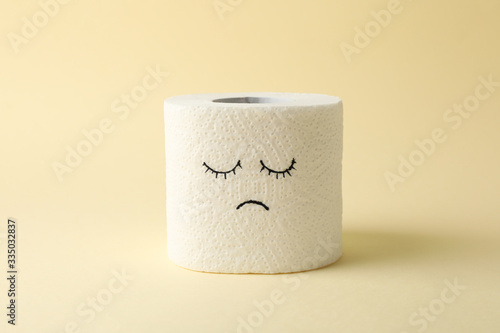 Toilet paper with sad face on beige background Canvas Print