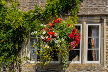 Beautiful Hanging Flowers Outside Window Of Vintage Stone House With Vines Surrounding It