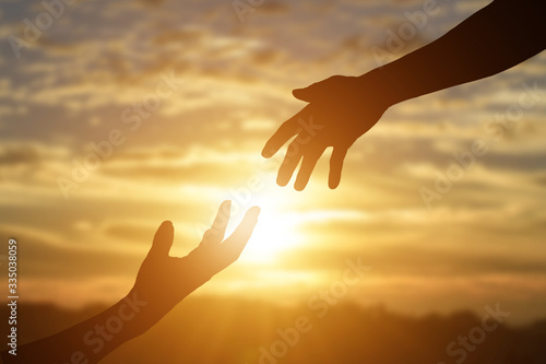 Valokuva Silhouette of giving a helping hand, hope and support each other over sunset background