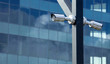 Two surveillance cameras mounted on a pillar in the background of a glass building