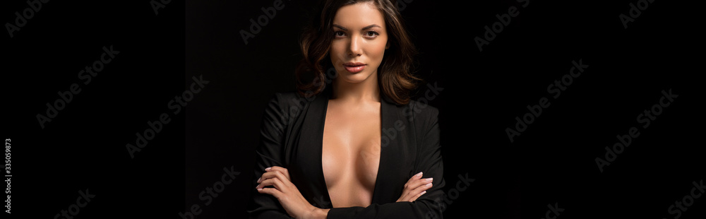 Fototapeta panoramic shot of confident, seductive girl in unbuttoned blazer posing with crossed arms isolated on black